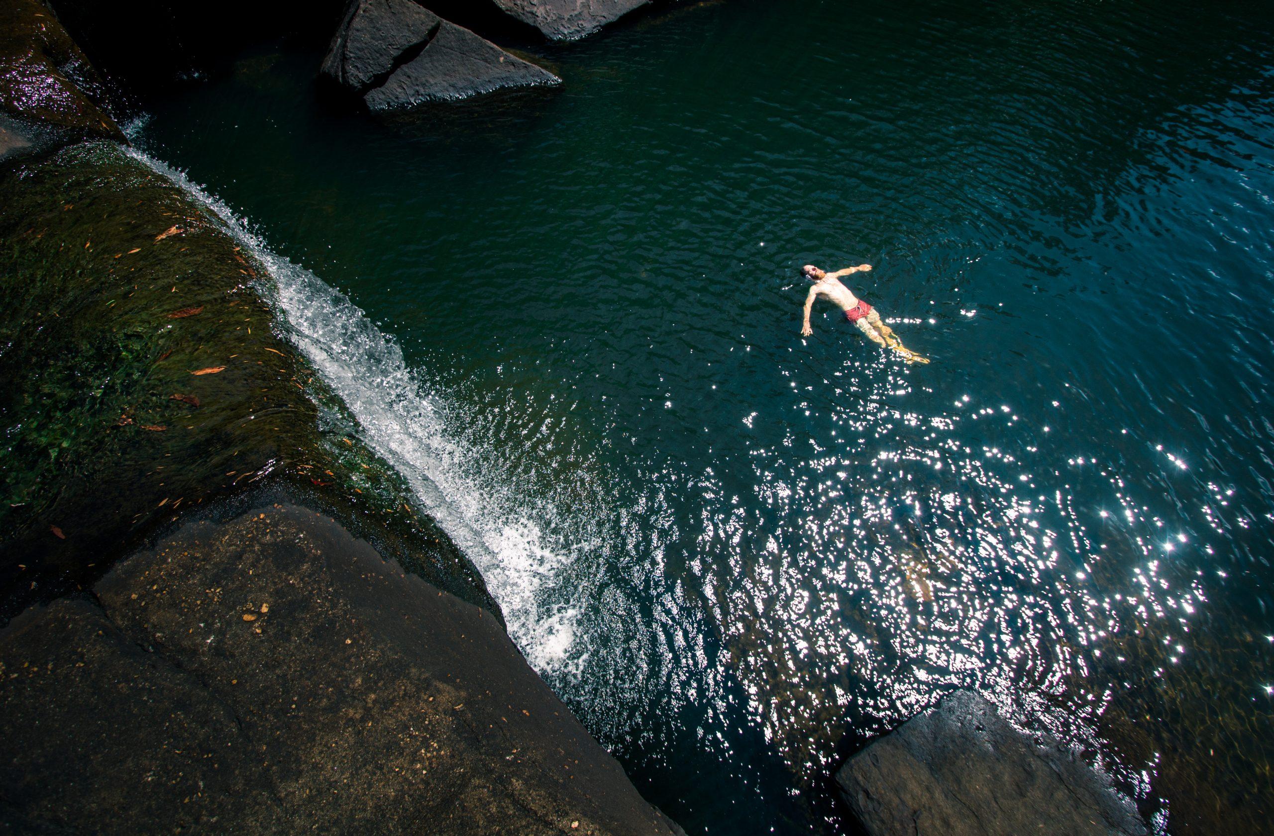 Man floating in Jingga Pool in Dharawal National Park